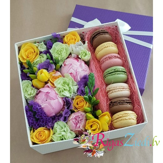 Box with fresh flowers and macaroons
