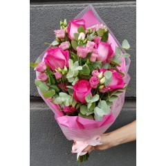 Bouquet of pink roses and lisianthus wrapped in decorative paper