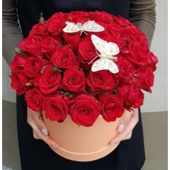 Red roses in a round box with butterflies